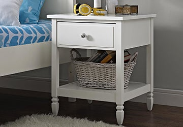 Small white nightstand beside a kid's bed