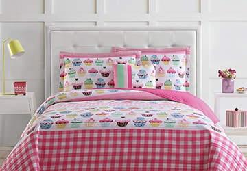 Pink quilt with a cupcake pattern on a child's bed