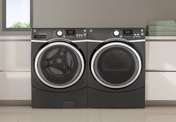 Matching black washer and dryer in a white laundry room