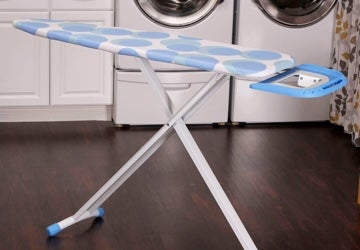 Ironing board set up in a laundry room