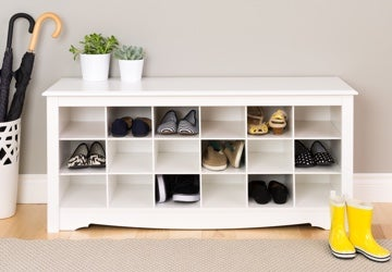 Shoe organizer with cubbies full of sandals, boots, and sneakers
