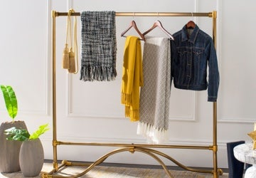 Golden garment rack with scarves, shawls, and jackets on hangers