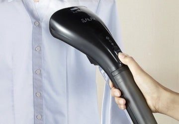 Garment steamer being used on a blue button-up shirt