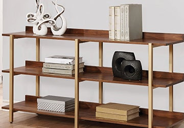 Wooden bookshelves holding books, sculptures, and accent boxes