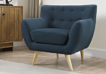 A blue living room chair with wooden legs and a button tufted back