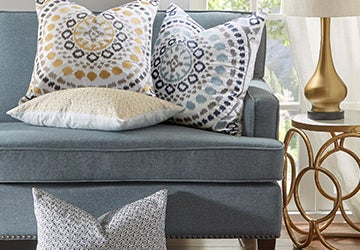 Elaborately patterned throw pillows, a polished table lamp, and other decorative accessories