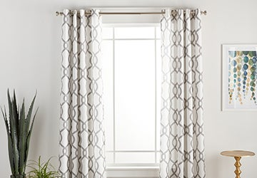 Geometric curtains on a golden curtain rod hanging over a window
