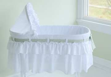 White bassinet in the corner of a nursery
