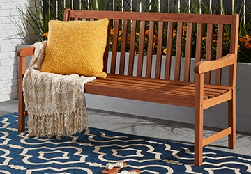 Wooden outdoor bench with a pillow and throw on a blue rug