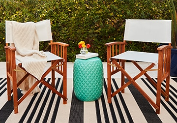 Turquoise accent table between two outdoor chairs in front of a hedge