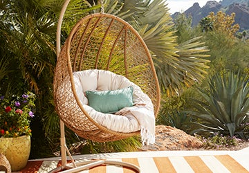 Wicker hanging chair with a plush cushion and a throw
