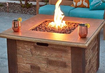 Lit propane fire pit with stone sides beside a patio bench with turquoise cushions