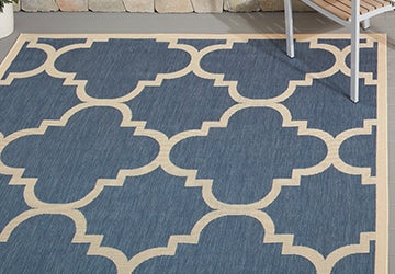 Closeup of a blue outdoor rug with a geometric beige pattern