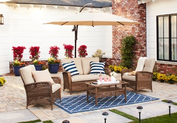 A brown patio set with beige cushions on a geometric blue outdoor rug
