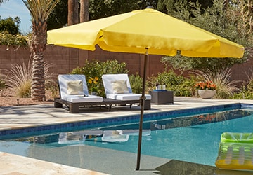 Yellow patio umbrella next to a swimming pool