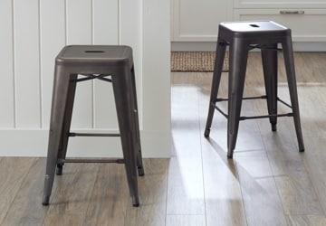 Two metal bar stools gathered around a white bar