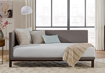 Minimalist daybed with throw pillows and an accent light