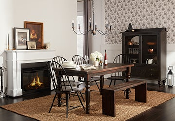 Wooden dinging table with colonial chairs on a jute rug beside a fireplace