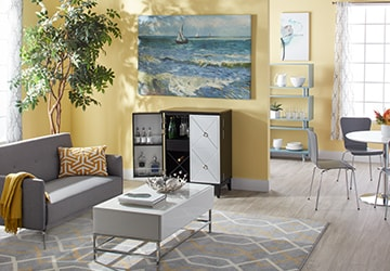 Living room with contemporary furniture and wall art depicting a seaside locale
