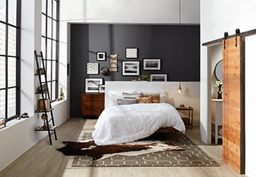 Studio bedroom with a leaning bookshelf, a cowhide rug, and a platform bed