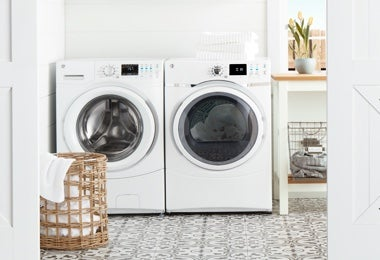 Laundry room with a washer, a dryer, and a laundry hamper