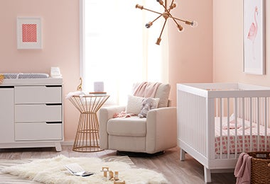 Pink nursery with a white crib, a dresser, and a comfortable chair