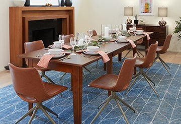 Festive dining table with brown chairs on a blue rug