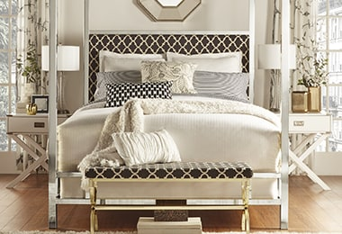 Bedroom featuring a glamorous bedframe with decorative pillows and comfortable blankets