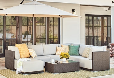 Cozy patio set with pillows and throws under a wide patio umbrella