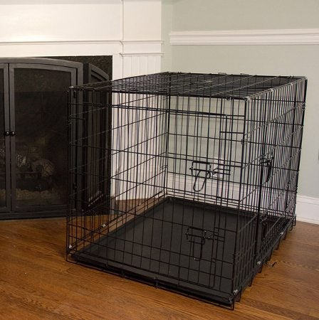 large, wire kennel set up by a living room fireplace