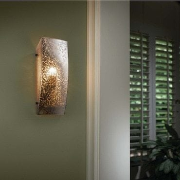 Wall sconce hanging on a green wall