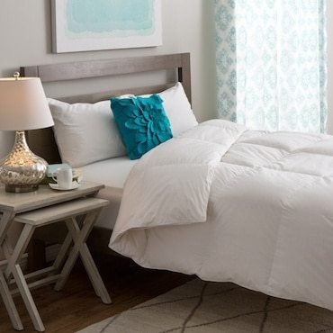White down comforter on brown bed