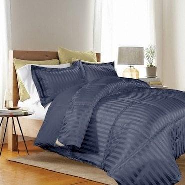 Blue Alternative Down Comforter on light brown bed