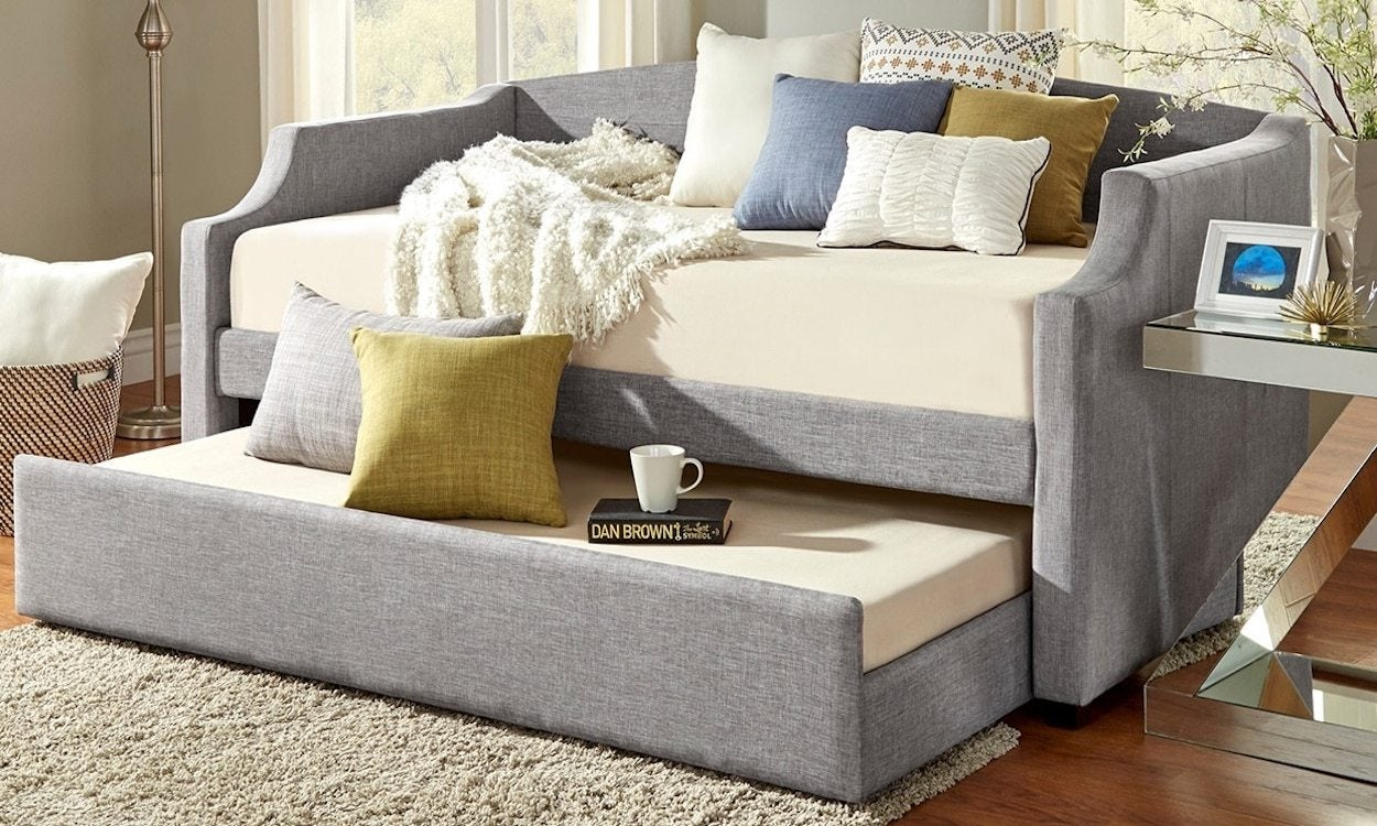 Grey trundle bed decorated with pillows