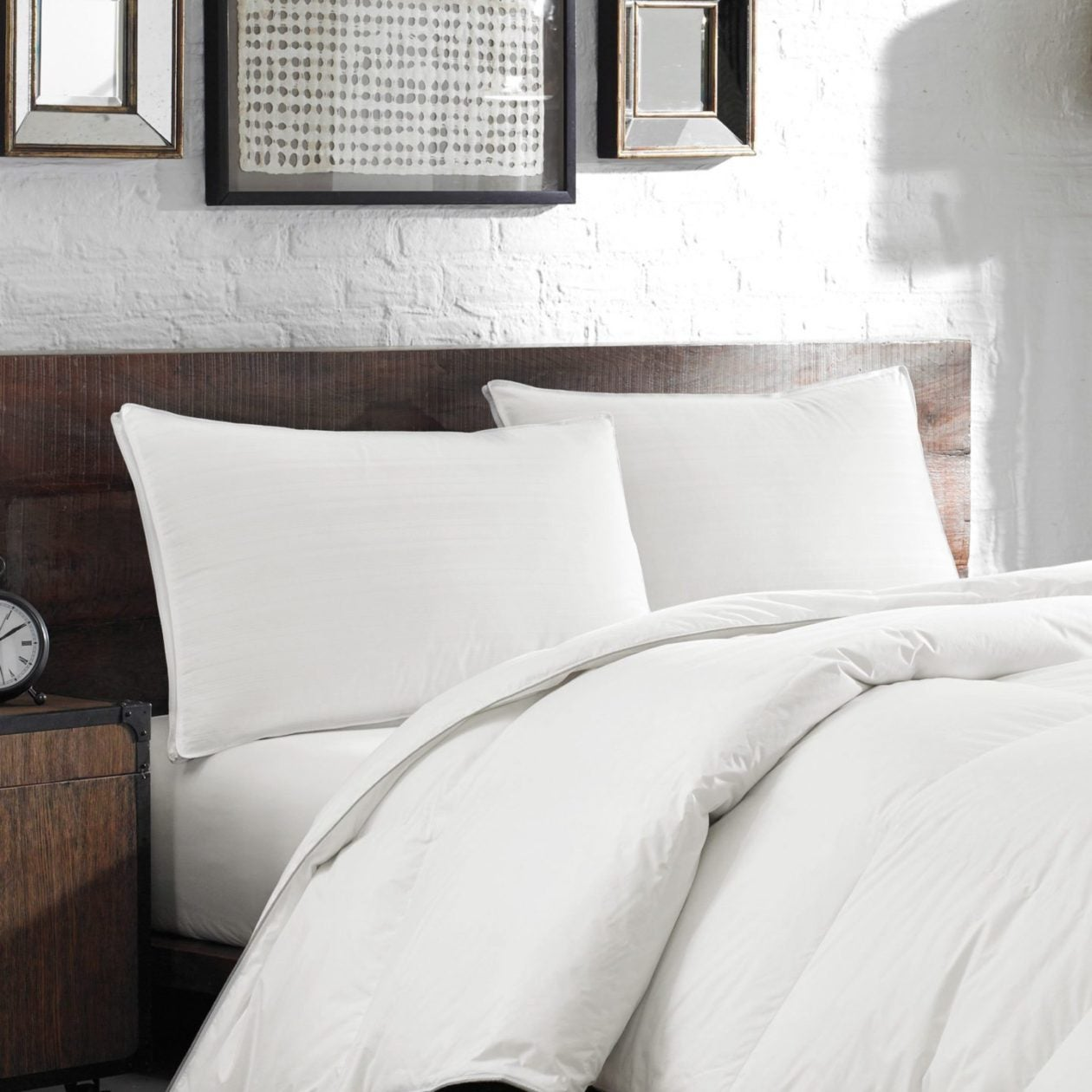 white pillows and white down bedding on brown bedrame
