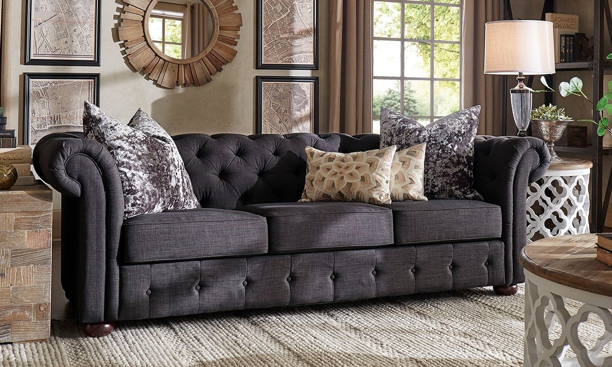Grey tufted sofa in living room.