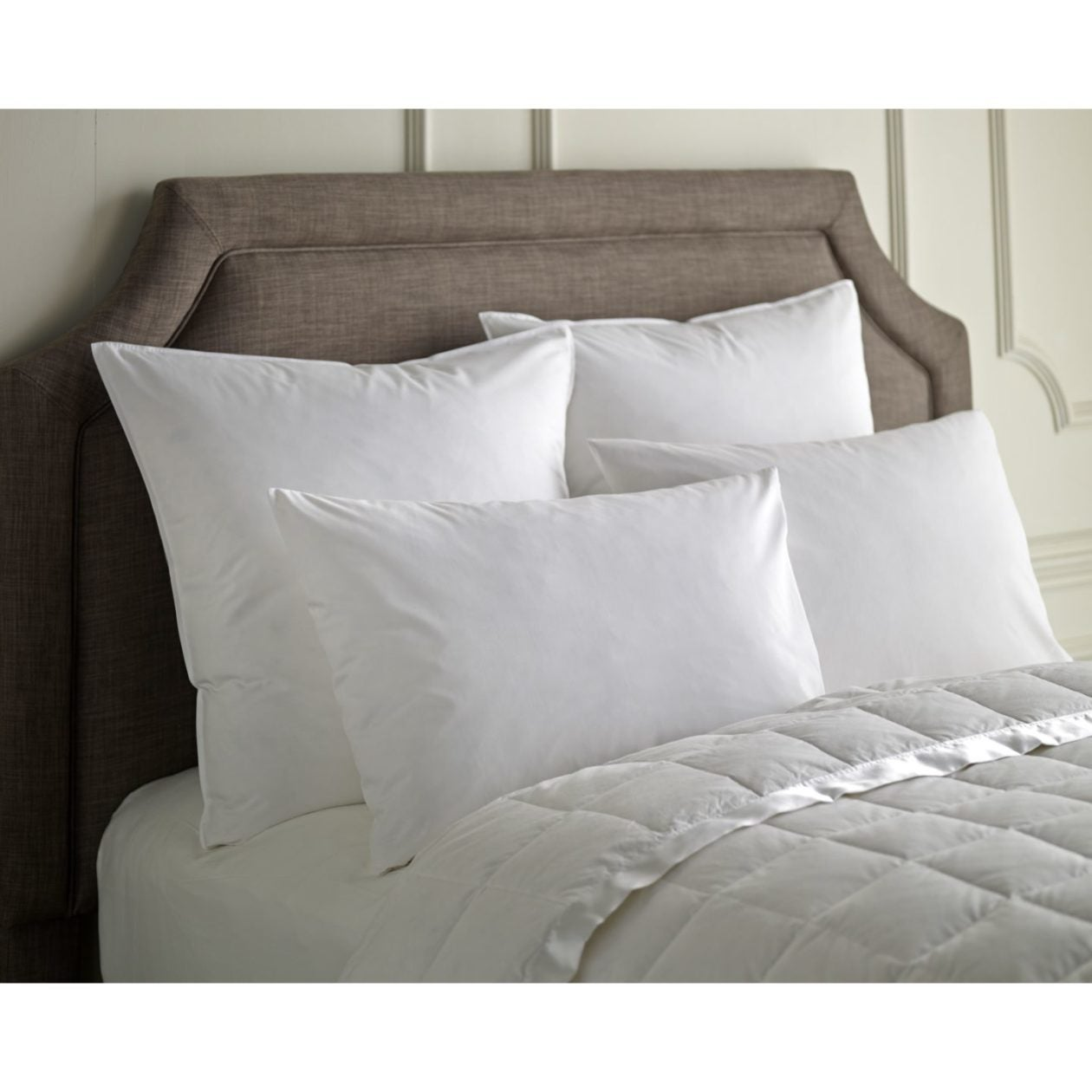 down pillows stacked neatly on white bed