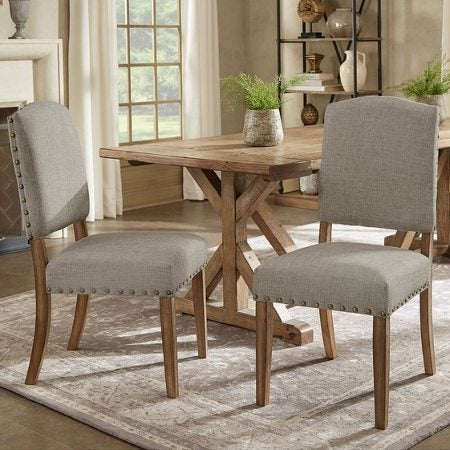two grey upholstered dining chairs at a wooden farmhouse table