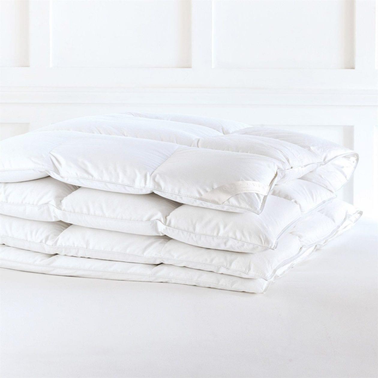 white folded down comforter on white background