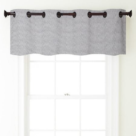 A black and white tailored valance hanging in a window