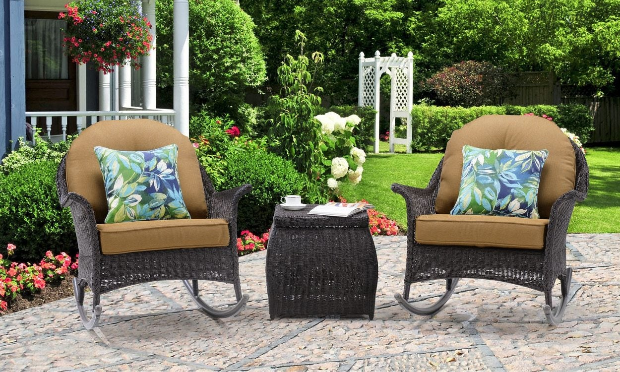 wicker rocking chairs with tan cushions on outdoor patio