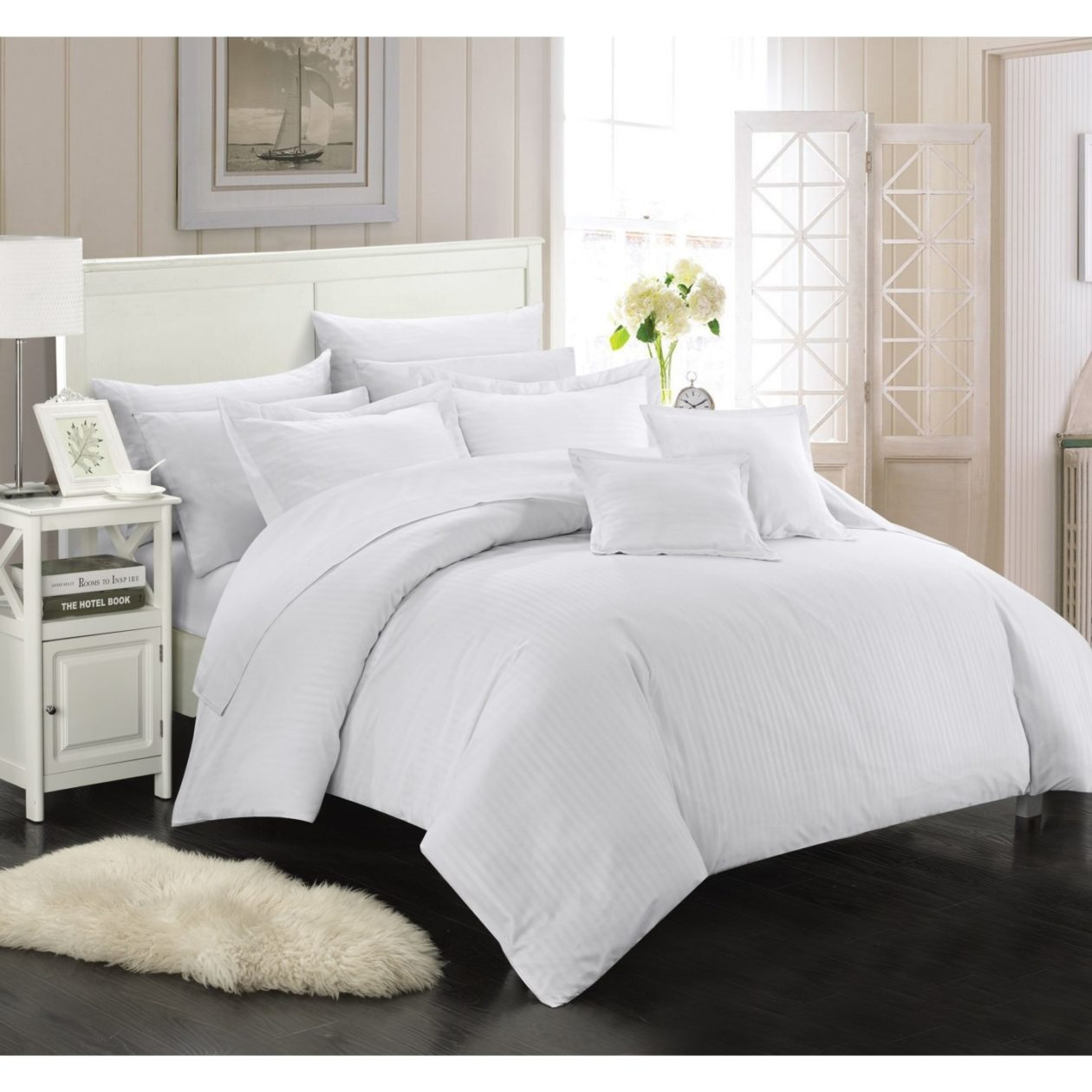 white down bedding neatly made on white bed frame