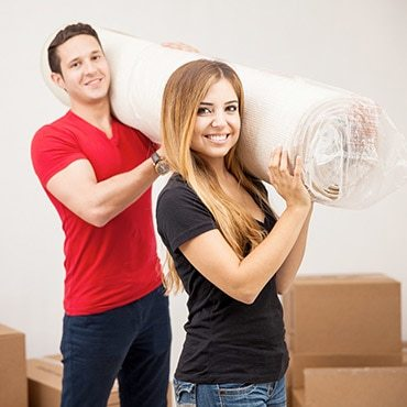 couple carrying an area rug