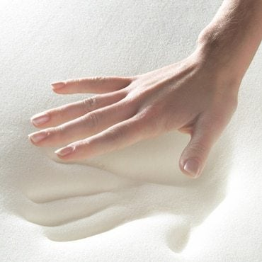 a hand pressing down on white memory foam