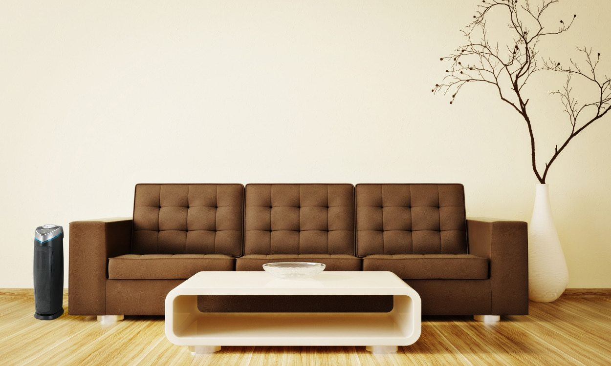 air purifier in living room with brown leather sofa