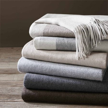 A stack of six folded wool throw blankets