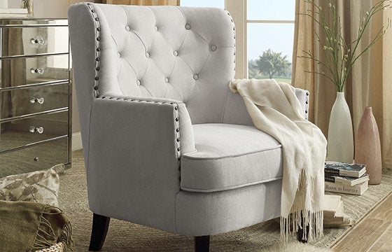 grey tufted accent chair with white throw blanket
