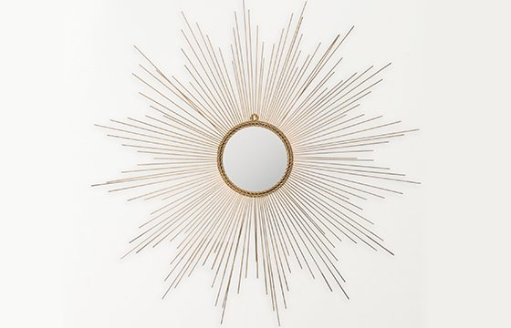 round mirror in a gold sunburst frame new home essentials