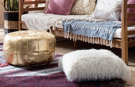Faux fur Floor Cushion and gold pouf ottoman on southwest rug boho chic living room ideas