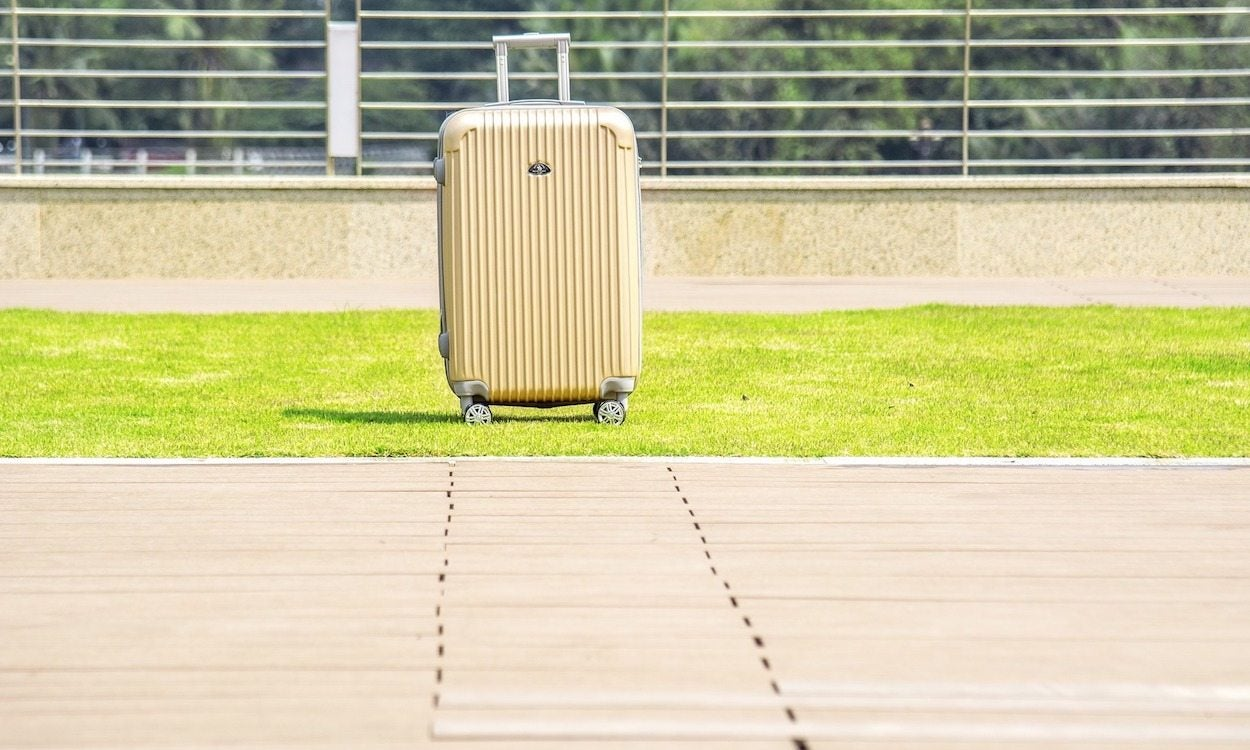 hard-sided luggage on wheels in the grass